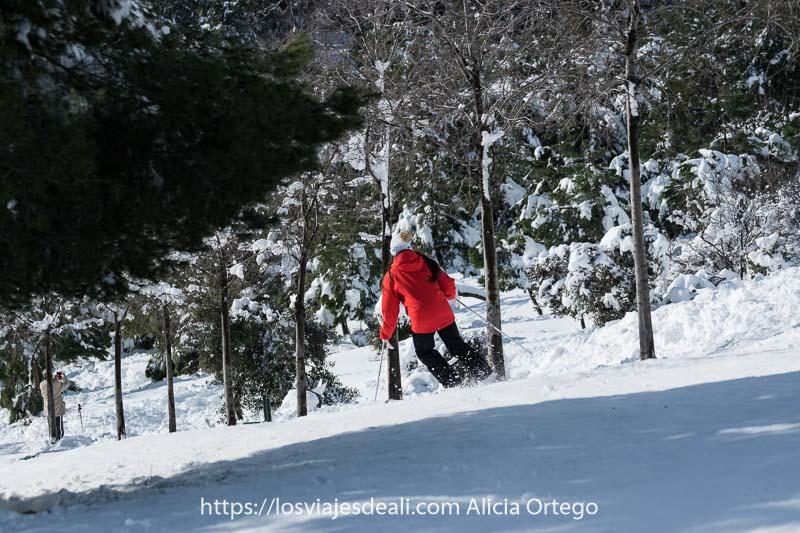 chica con chaqueta roja esquiando en una ladera del parque