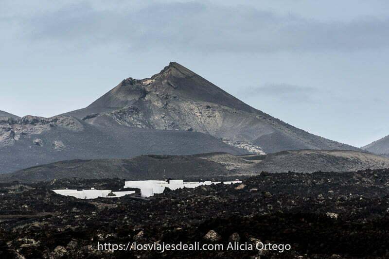 gran volcán de color negro y gris y unas casas blancas en medio de un campo de lava negra a sus pies
