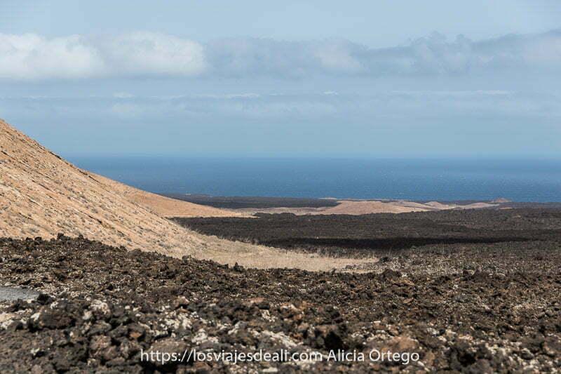 vista de campos de lava de color negro y beige con el mar al fondo practicando senderismo en lanzarote
