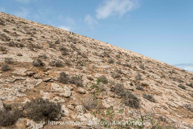ladera de la caldera blanca muy empinada de color beige y blanco con gente practicando senderismo en lanzarote