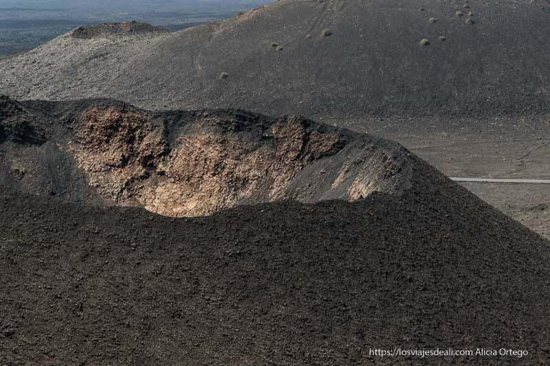 gran cráter de color negro con paredes interiores amarillentas en el parque nacional de timanfaya