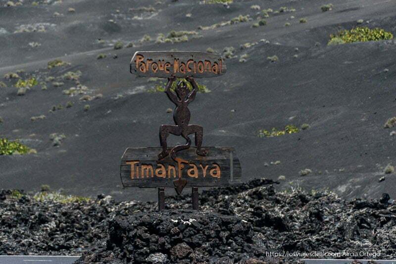 cartel del parque nacional de timanfaya con diablo con brazos en alto y cola entre las piernas