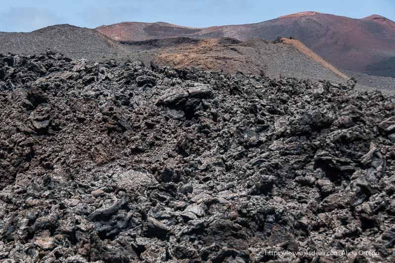 lavas retorcidas en primer plano de color gris y al fondo volcanes rojizos