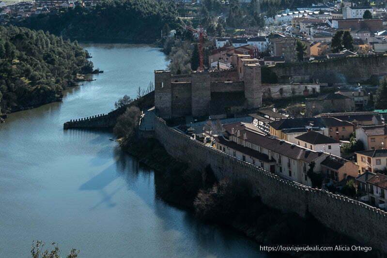 vista desde arriba de parte de las murallas de Buitrago del Lozoya con el castillo y sus torres junto al río
