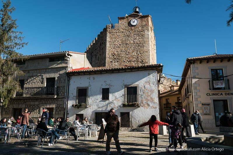 plaza de la torre del reloj con gente sentada en una terraza al sol