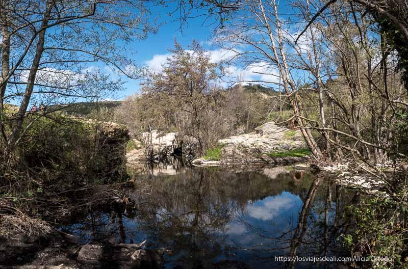 lago donde se reflejan los árboles en un día despejado de camino a la Cascada del Hervidero
