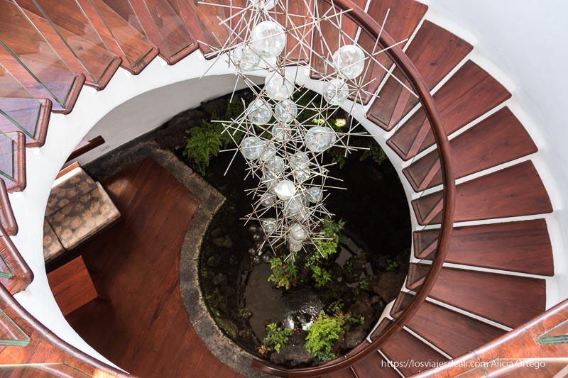 escaleras de caracol con una lámpara en el centro con forma de espinas y bombillas redondas obra de césar manrique
