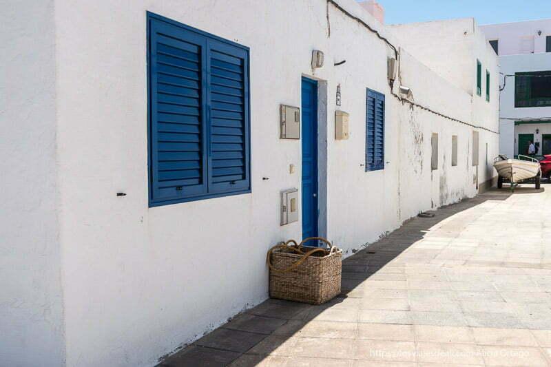 calle de famara con casas blancas con puertas y ventanas azules