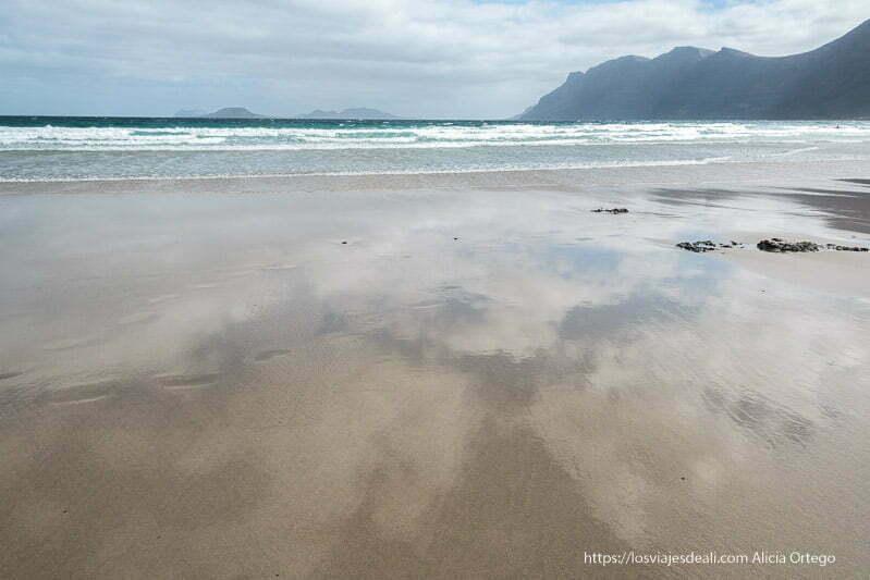 reflejo de nubes en la arena mojada de famara con los riscos al fondo