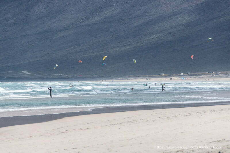 caleta de famara con gente practicando kitesurf y agua con muchas olas