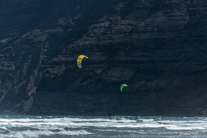 dos velas de kitesurf de color amarillo y verde se recortan en el fondo de acantilados negros