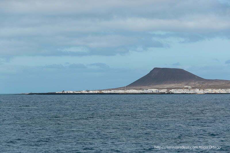 población de La Graciosa de casas blancas vista desde el mar de lejos con perfil del volcán