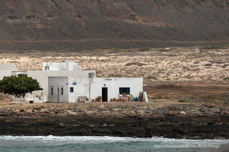 casa blanca con mesa y sillas de madera enmedio de paisaje desértico de La Graciosa