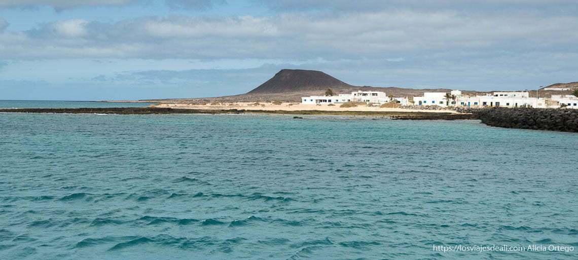 mar de color turquesa con la isla de La Graciosa, casas blancas y volcán