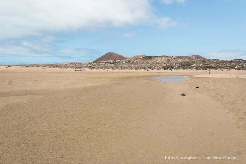 playa ancha de arena dorada con volcanes al fondo en La Graciosa
