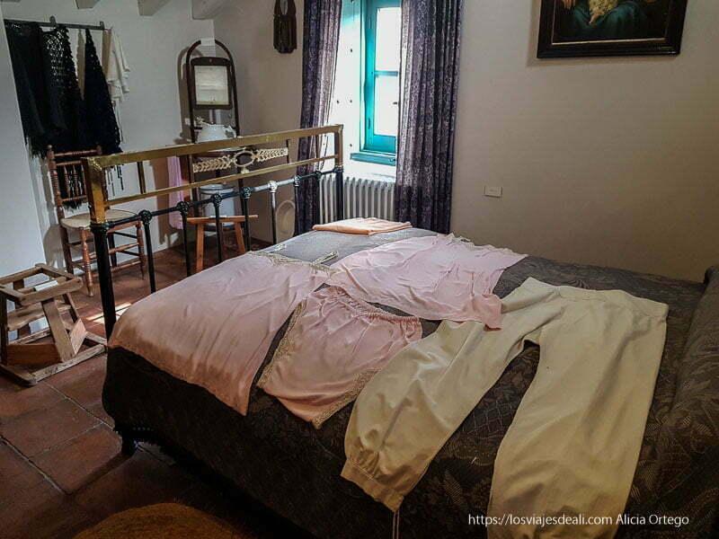dormitorio antiguo con ropa interior de la época sobre la cama
