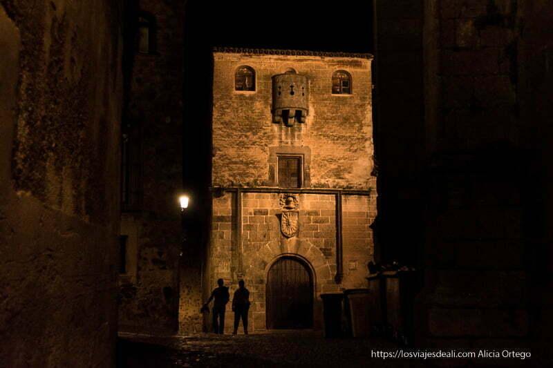 torreón con puerta con escudo y pequeño balcón semicircular en la parte superior en la noche de Cáceres