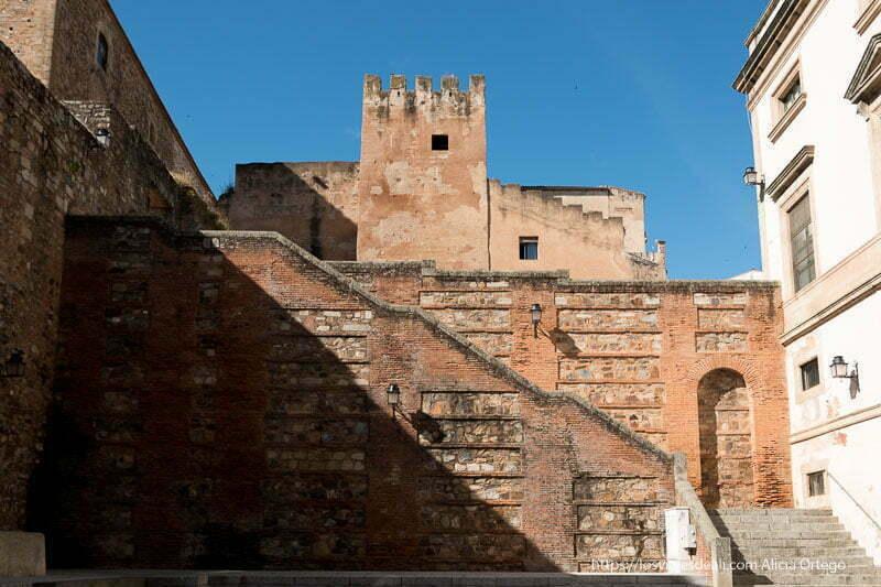 escaleras en un muro de ladrillo y piedra y torre almenada con cielo azul