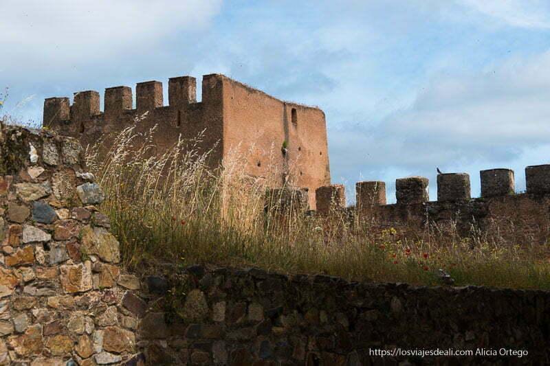muralla y torre de color anaranjado en el atardecer