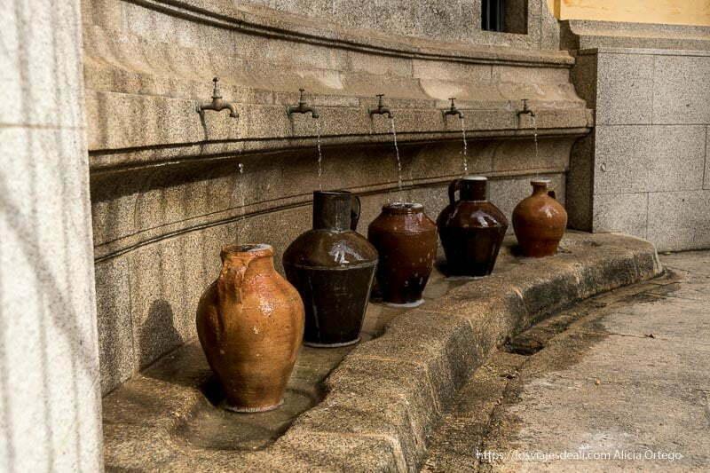 fuente con cinco caños y cinco vasijas de barro grandes recogiendo el agua