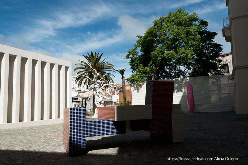 patio del museo helga de alvear con un banco revestido de azulejos de colores y un árbol seco pintado de blanco