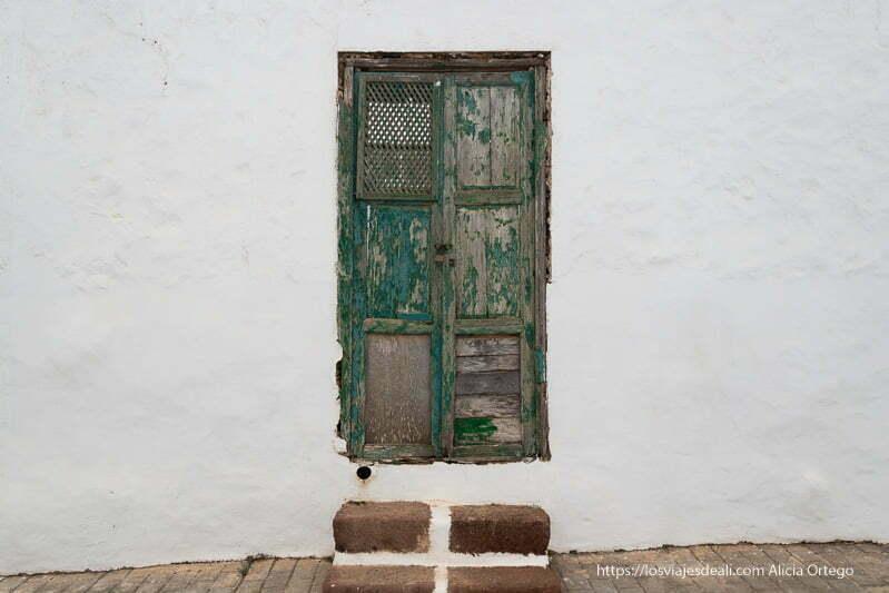 puerta vieja de madera con un panel de celosía y dos escalones para entrar