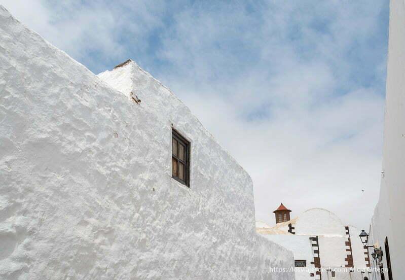 muros blancos recortándose en cielo azul con nubes blancas