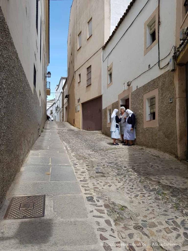 calle de cáceres en cuesta y dos monjas hablando con una mujer en la puerta de su casa