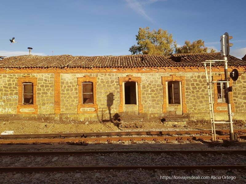 vista desde el tren de estación abandonada hecha en piedra y ladrillo y cigüeña volando sobre el tejado