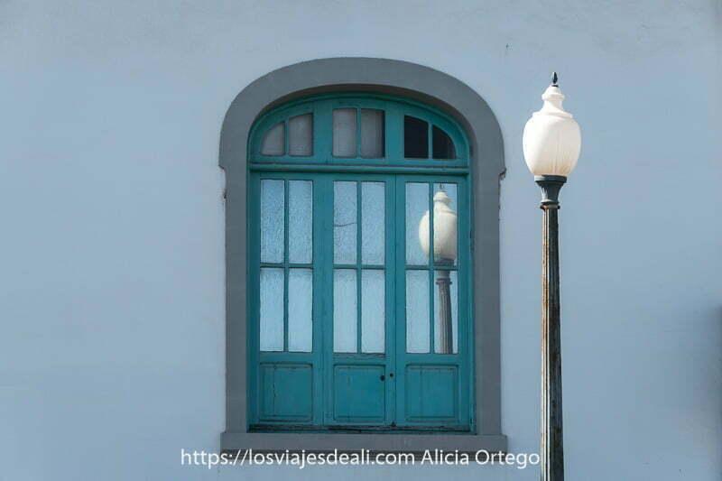 ventana en forma de arco con farola al lado que se refleja en los cristales