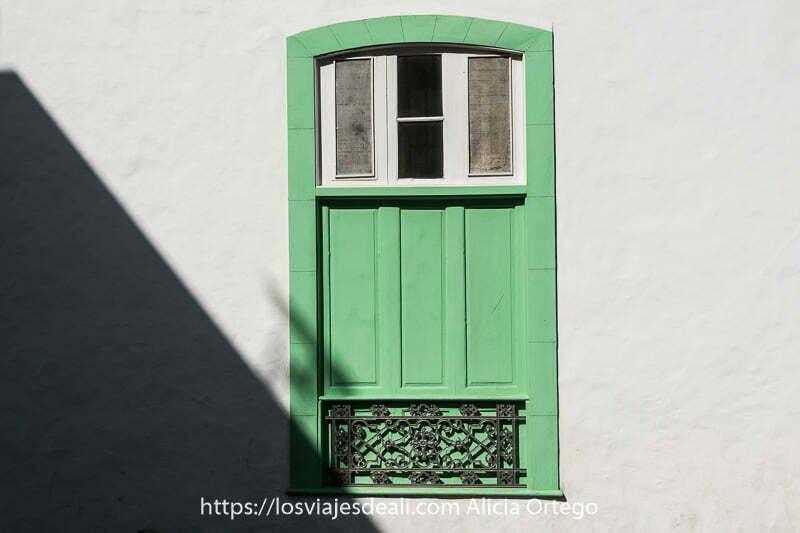 ventana de madera pintada de verde en muro blanco