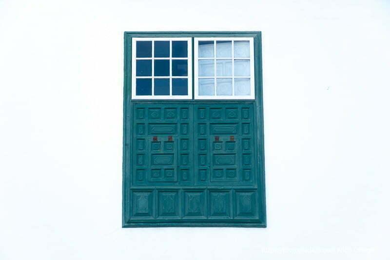 ventana de madera pintada de verde con cuarterones con cristales en parte superior