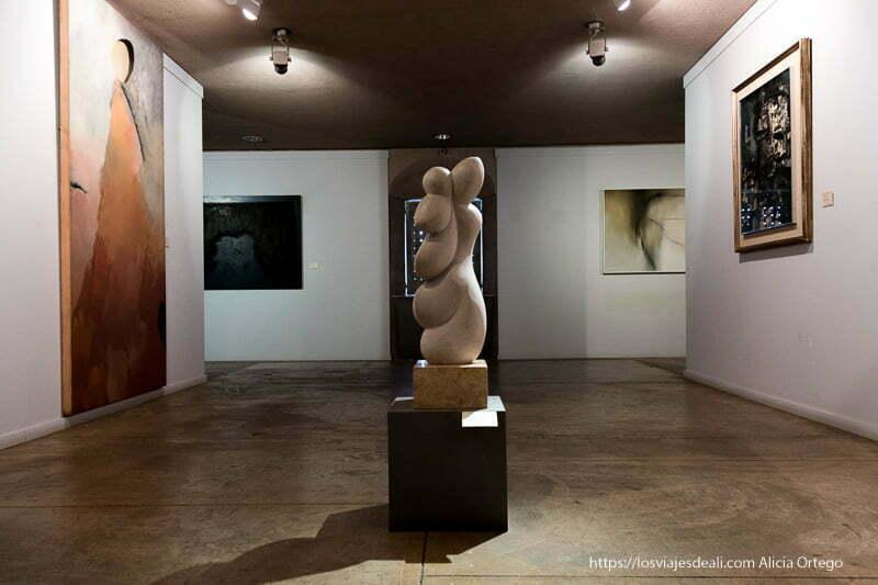 sala de arte moderno del museo de cáceres con cuadros y una escultura en el centro con formas redondeadas