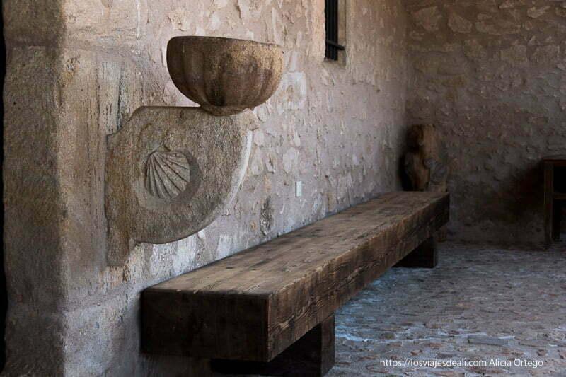 banco de madera y un cuenco de piedra con agua bendita adosado a la pared con la concha del camino de santiago