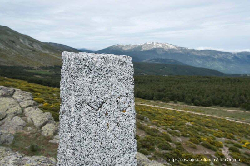 hito de piedra de granito con montañas al fondo con un poco de nieve