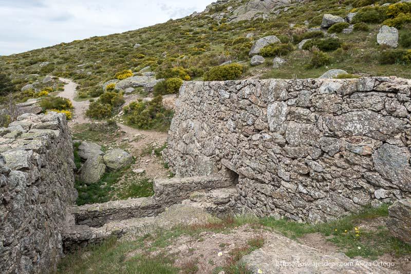 antiguo molino de piedra con forma trapezoidal adaptándose a la forma de la montaña