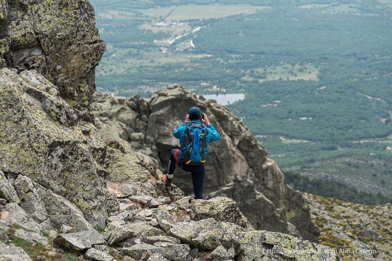 excursionista haciendo una foto del valle entre rocas en la ruta a la loma de los bailanderos