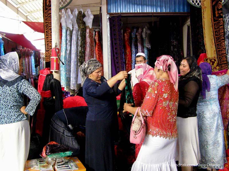 mujeres con pañuelos de colores en la cabeza examinando telas de colores en un mercado