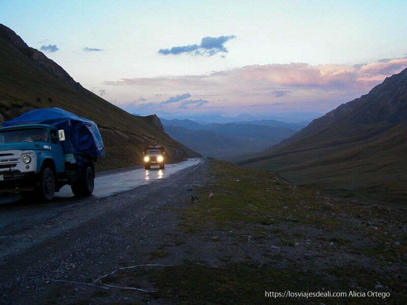 carretera de montaña al atardecer con dos camiones viejos que circulan con luces encendidas y nubes rojizas en la ruta de la seda