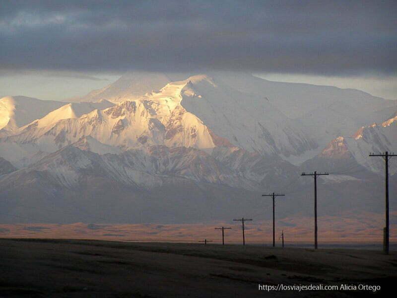 amanecer con las montañas del pamir nevadas iluminadas por el sol y una hilera de postes de la luz