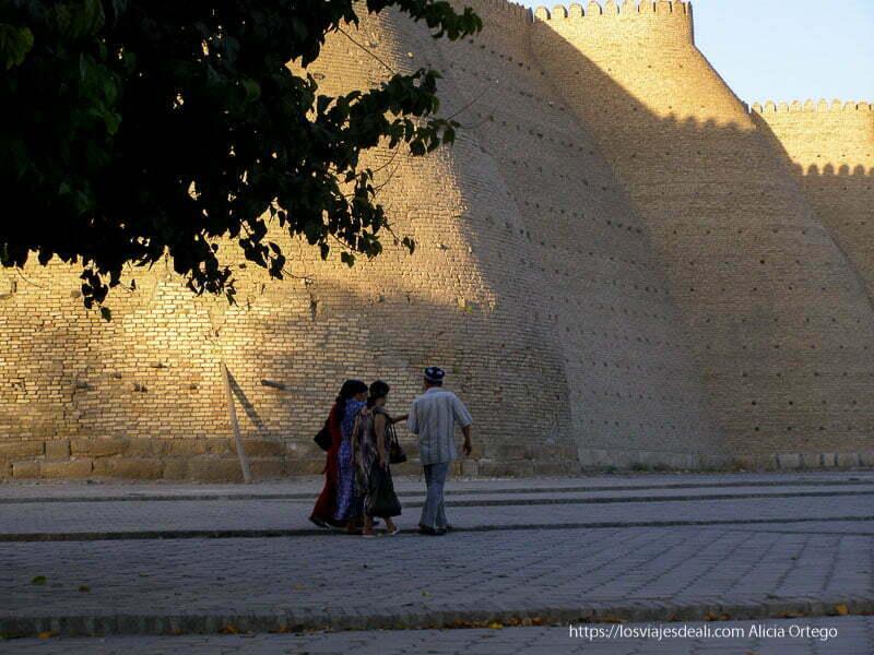 tres mujeres con vestidos y un hombre paseando junto a las murallas de ladrillo de Bukhara