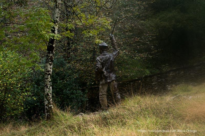 escultura de un pastor con boina y bastón alzado en el salto del nervión