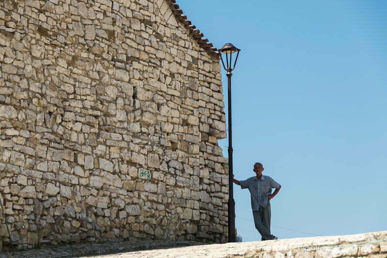 hombre apoyado en una farola junto a muro de piedra en el viaje a Albania