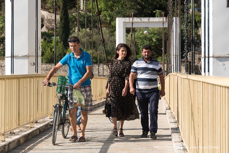 dos hombres y una mujer cruzando un puente en Berat