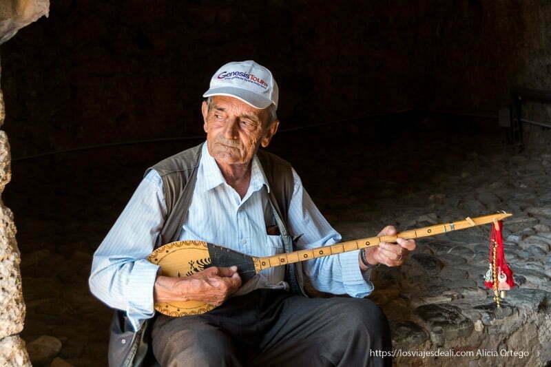 señor mayor tocando un instrumento tradicional de dos cuerdas