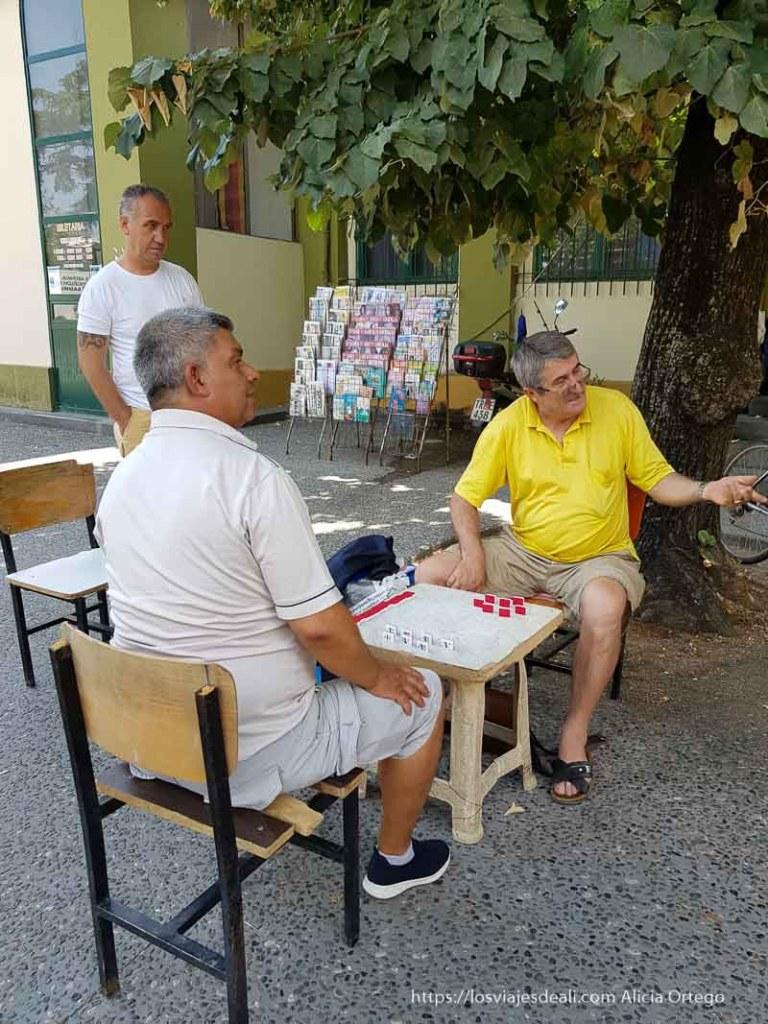 dos hombres jugando al dominó en la calle y uno mirando en Tirana