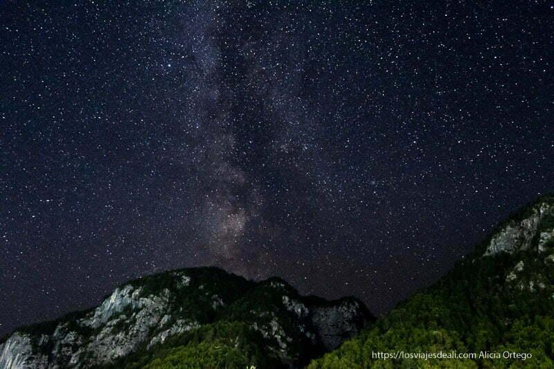 vía láctea sobre montañas con bosques y paredes rocosas en el viaje a Albania