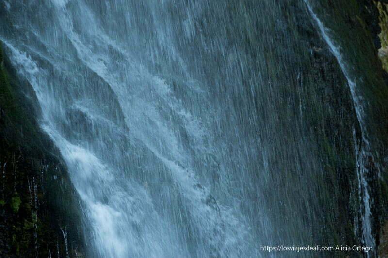 agua de la cascada cayendo sobre las rocas en el valle de theth