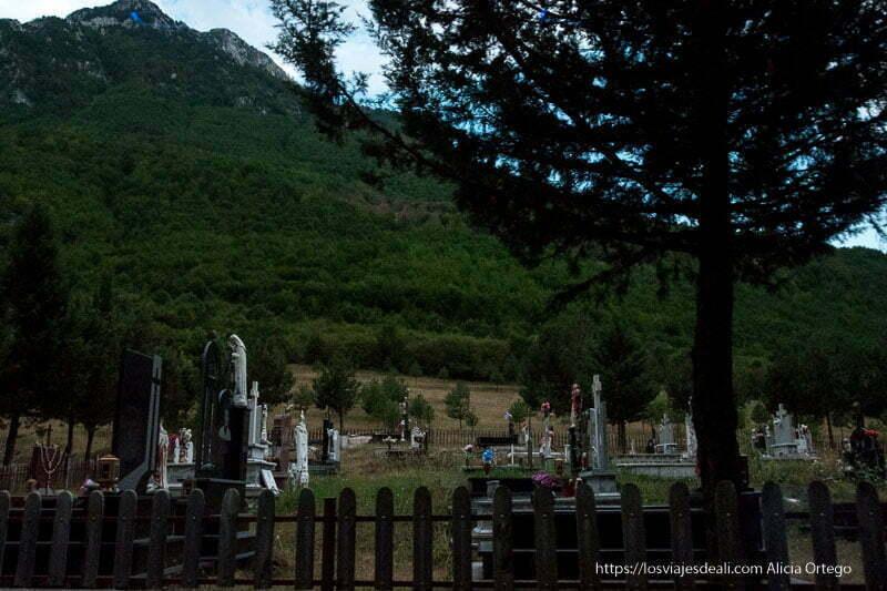 cementerio con tumbas con flores y valla de madera de camino al valle de theth
