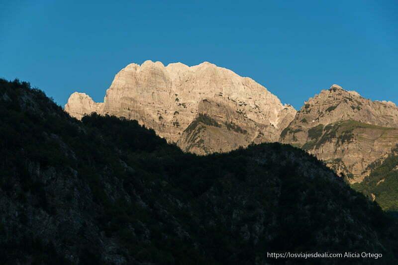 picos rocosos dentados iluminados por sol poniente anaranjados en valle de theth